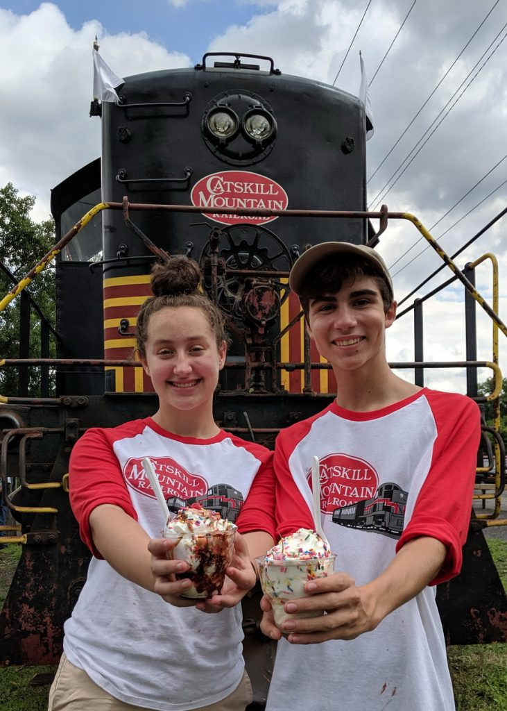 2 teens holding ice cream in front of train