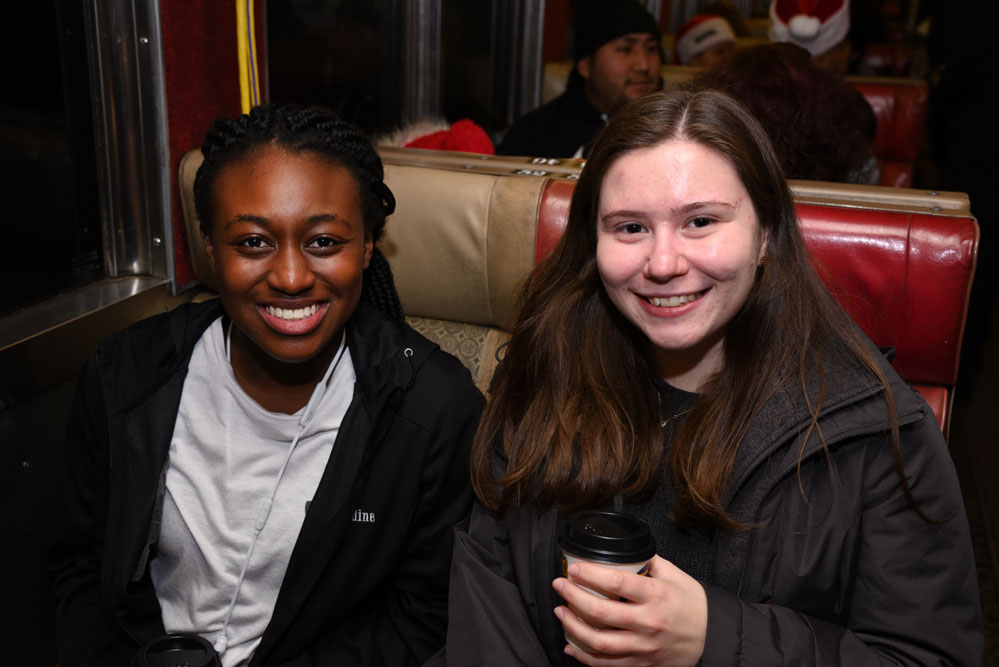 Two smiling friends aboard the Polar Express