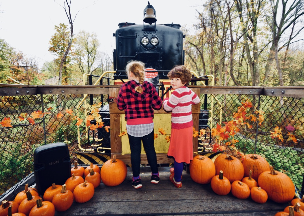2 kids in front of train with pumpkins