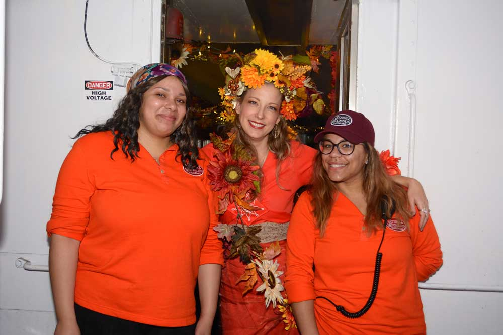lady dressed in fall decor with 2 staff