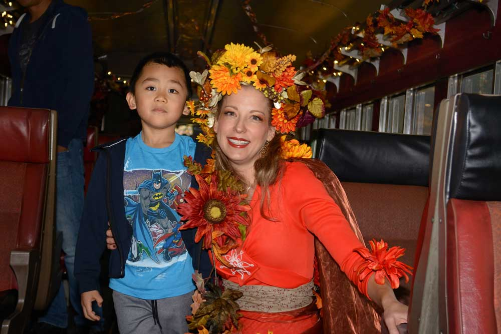 lady dressed in fall decor with kid