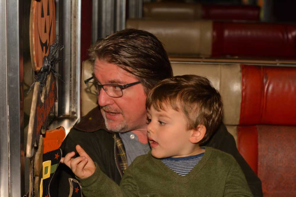 father holding son on train looking at pumpkin decorations