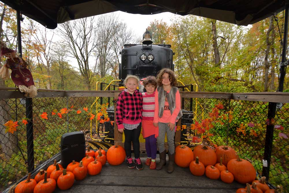 3 kids in front of train with pumpkins