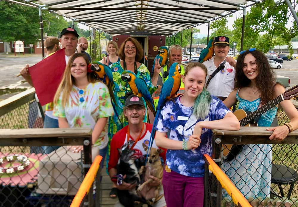 staff of peace train posing with parrots