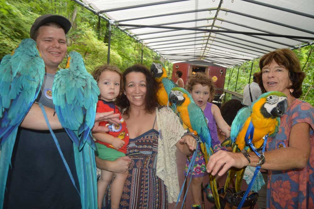 family posing with parrots on peace train