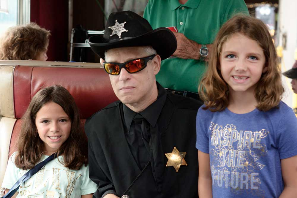 man in sheriff outfit with 2 kids