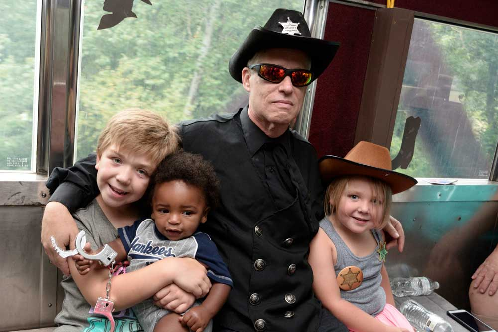 man in sheriff outfit with 3 kids