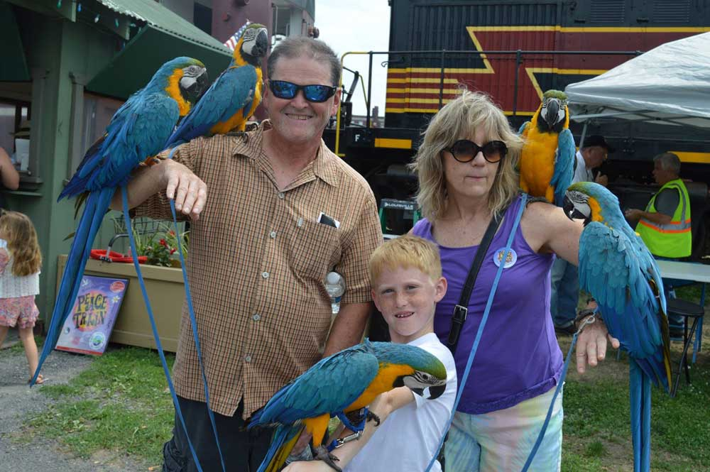 family posing with parrots in front of train