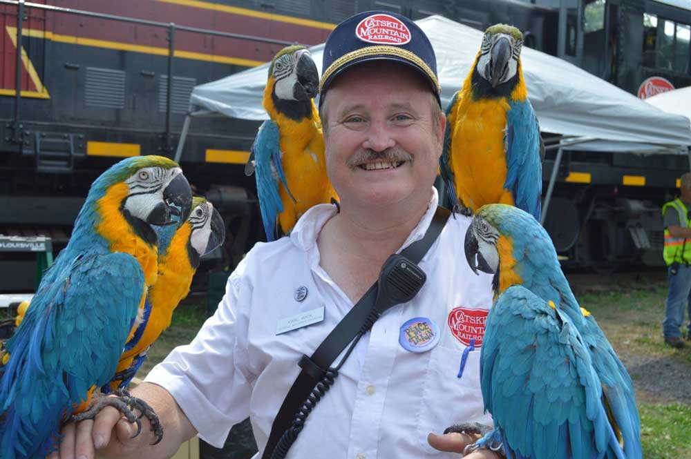 conductor posing with parrots in front of train